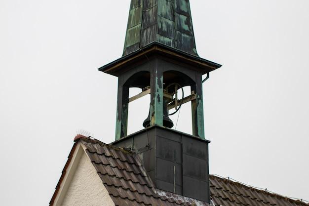 Catholic church bell tower against a overcast sky.