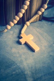 Catholic rosary beads with old book on cement table prayer, rosary background  in vintage tone.