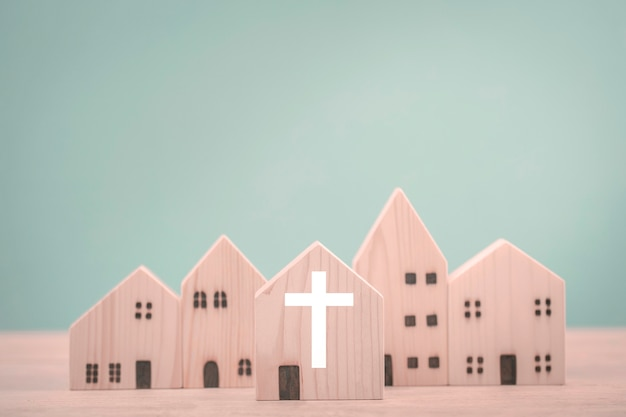 Catholics church and village made of wooden houses on mint background