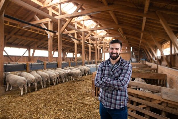 Работник фермы скотовода в повседневной одежде позирует со скрещенными руками в деревянном сарае для скота.