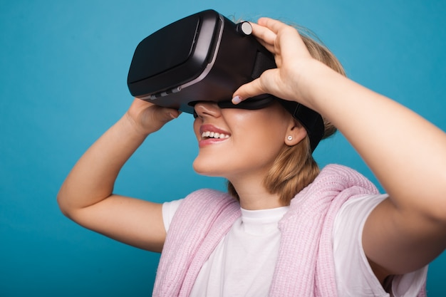 Caucasia woman with blonde hair is testing new vr glasses and smile on a blue studio wall