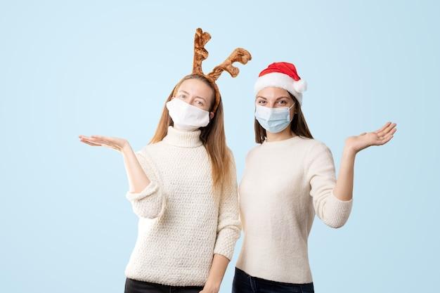 サンタの帽子とトナカイと白のコーカシアムの若い女性。