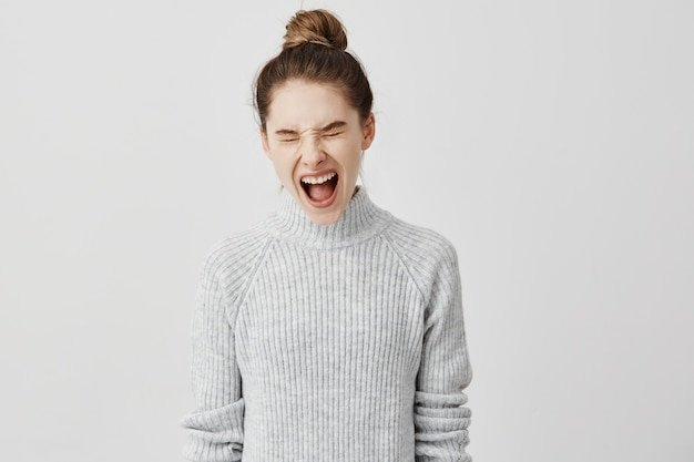 Caucasian adult girl screaming with her eyes screwed up. disappointed female passenger shouting loudly being in trouble. people and reaction concept