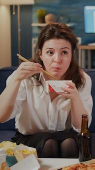 Кавказский взрослый смотрит на телевизор во время еды китайской еды и пьет пиво из бутылки, сидя на диване в гостиной. молодая женщина, наслаждаясь азиатской едой и напитками дома после работы