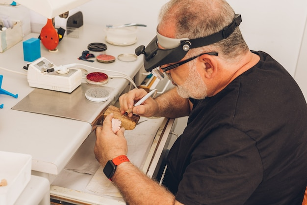 ワックスでセラミック歯科用金型を成形するポーセレンクラウンを作成する歯科技工所のワークショップに座っている顔面保護の白人成人男性