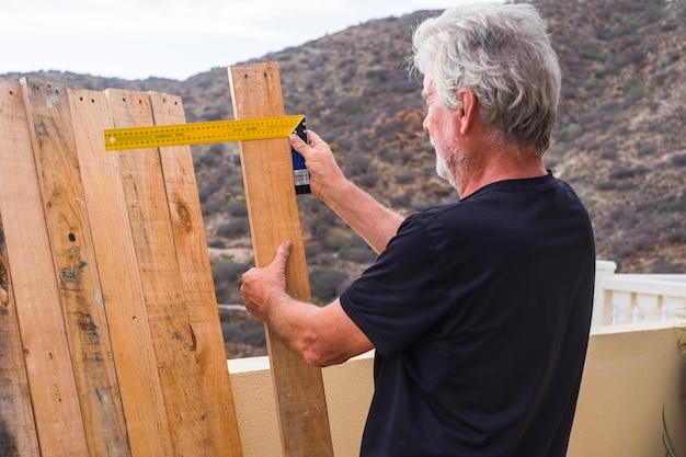 백인 성인 수석 은퇴 한 남자가 팔레트에서 재활용 된 나무로 테이블이나 바닥을 짓는 집에서 작업-레저 활동 수리 또는 사람들을위한 개념 구축