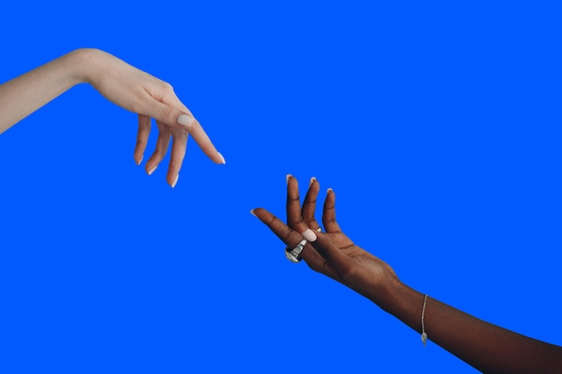 Caucasian and african american hand reaching out to each other.