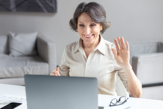 Caucasian aged business woman waves hand, greets the participants in the video conference, used laptop computer to communicate online sitting in the office or at home. video call, remote work concept