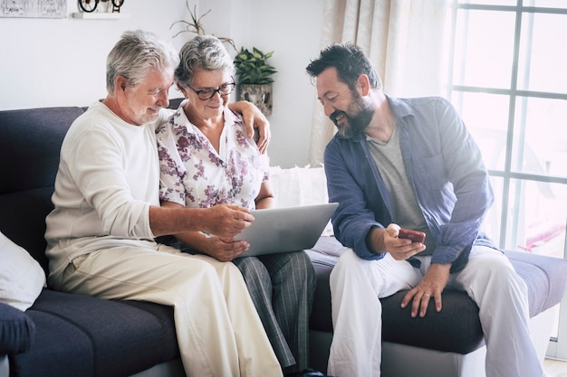 Caucasian aged family at home matures and middle age people together using technology devices like laptop and mobile phone enjoying internet web results