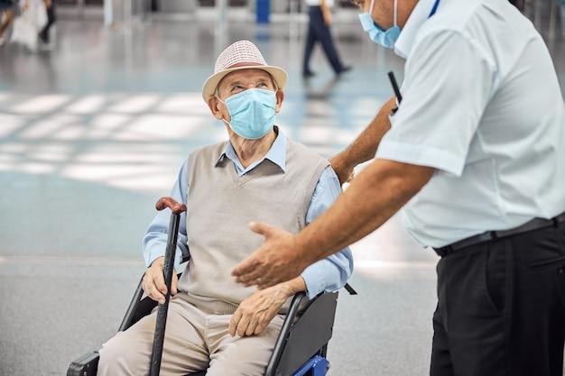 장애인 노인에게 뭔가를 설명하는 보호 마스크에 백인 항공사 남성 직원