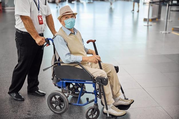 얼굴 마스크에 수석 장애인 승객과 수송 의자를 압 연 백인 공항 남성 직원