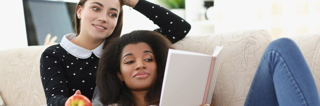 白人とアフリカ系アメリカ人の女性はソファで手帳を読む