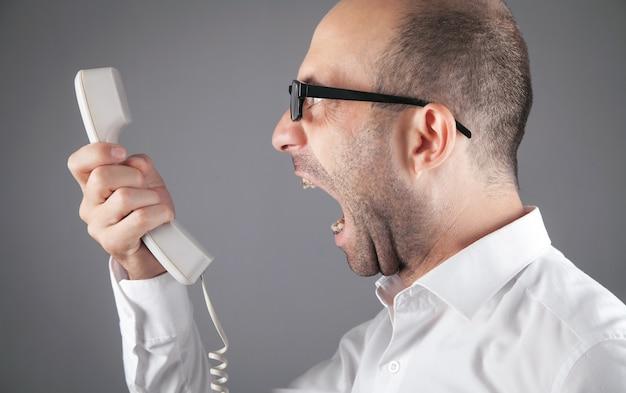 白人の怒っているビジネスマンが受話器に向かって叫びます。