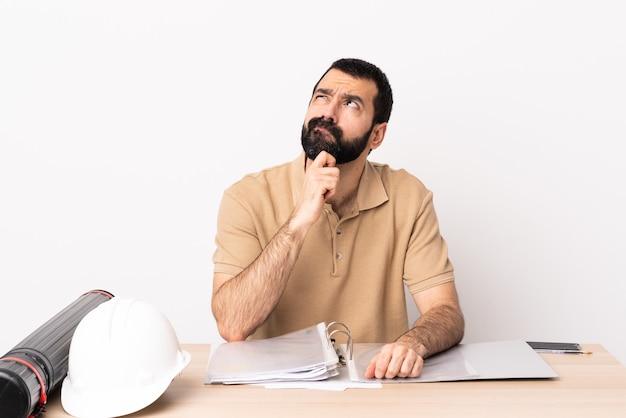 テーブルと見上げるひげを持つ白人建築家男。