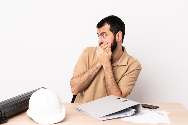 입을 덮고 측면을 찾고 테이블에 수염을 가진 백인 건축가 남자.