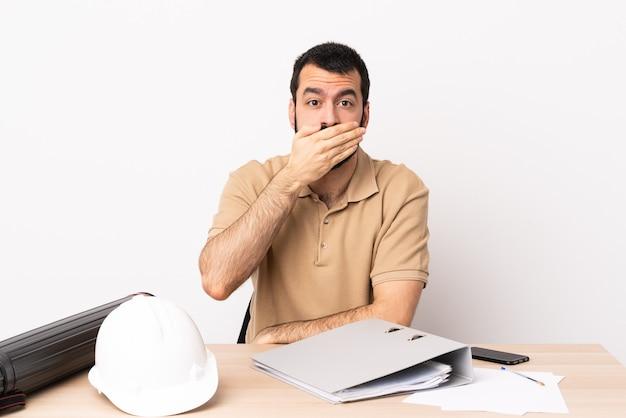 손으로 입을 덮고 테이블에 수염을 가진 백인 건축가 남자.