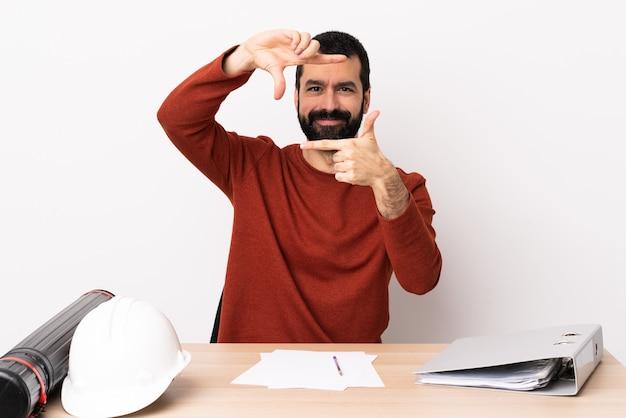 얼굴을 집중하는 테이블에 수염을 가진 백인 건축가 남자. 프레임 기호