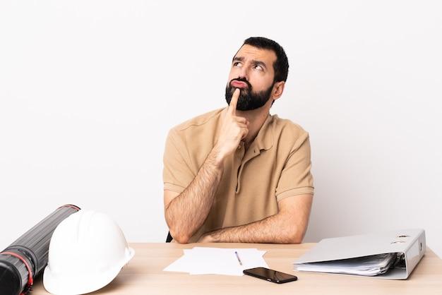 Кавказский архитектор мужчина с бородой в таблице сомневается, глядя вверх.