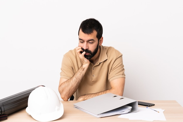 의심을 갖는 테이블에 수염을 가진 백인 건축가 남자.