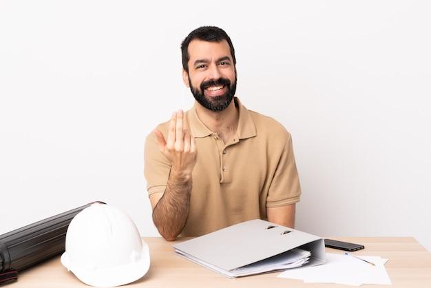 손으로와 초대 테이블에 수염을 가진 백인 건축가 남자. 네가 와서 기뻐