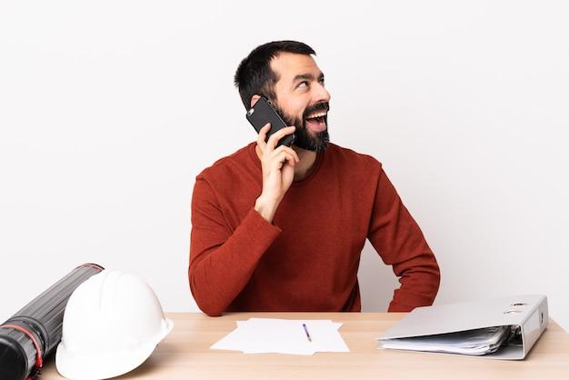 휴대 전화와 대화를 유지하는 테이블에 수염을 가진 백인 건축가 남자