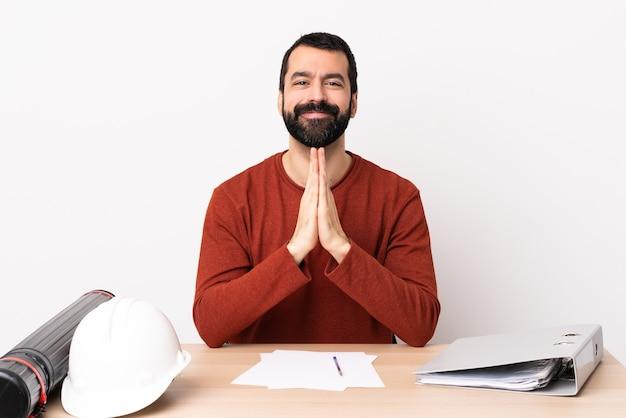 테이블에 수염을 가진 백인 건축가 남자는 손바닥을 함께 유지합니다. 사람이 무언가를 요구합니다.