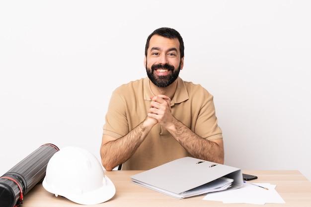 웃으면 서 테이블에 수염을 가진 백인 건축가 남자