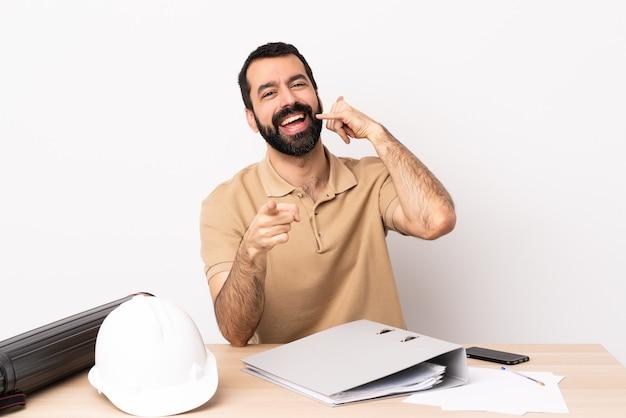 전화 제스처를 만들고 앞을 가리키는 테이블에 수염을 가진 백인 건축가 남자.