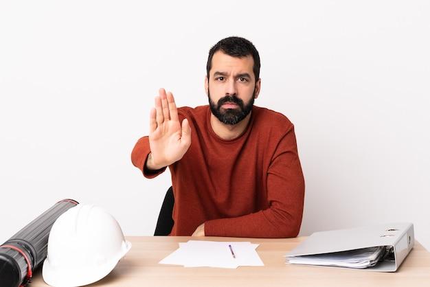 Кавказский архитектор мужчина с бородой в таблице, делая стоп-жест.