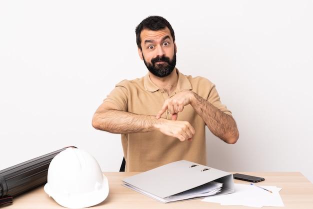 늦은 제스처를 만드는 테이블에 수염을 가진 백인 건축가 남자.