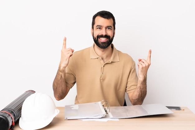 좋은 아이디어를 가리키는 테이블에 수염을 가진 백인 건축가 남자