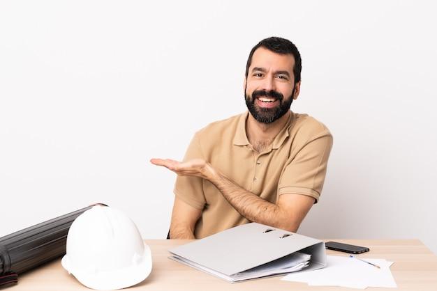 향해 미소를 보면서 아이디어를 제시하는 테이블에 수염을 가진 백인 건축가 남자