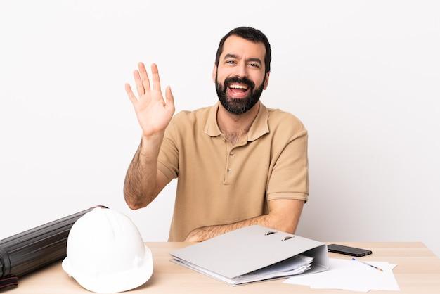 幸せな表情で手で敬礼するテーブルにひげを持つ白人建築家の男。