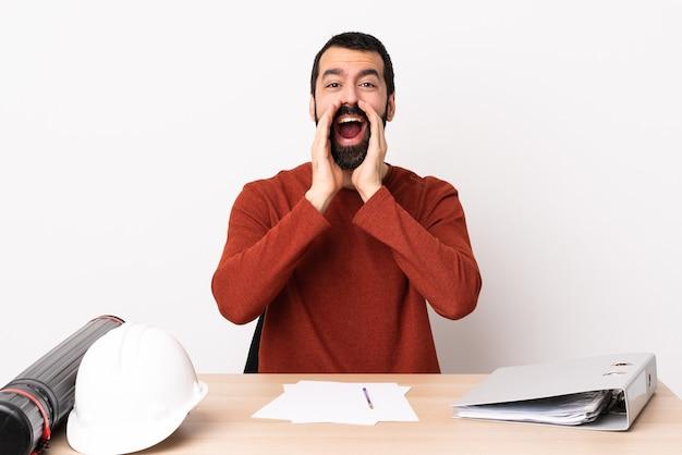 何かを叫び、発表するテーブルにひげを生やした白人建築家の男。