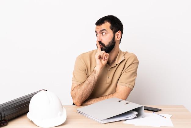 Кавказский архитектор мужчина с бородой в таблице показывает знак жеста молчания, положив палец в рот.