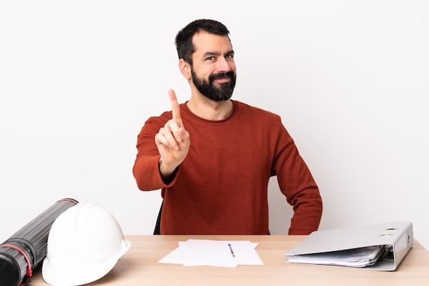 표시 하 고 손가락을 드는 테이블에 수염을 가진 백인 건축가 남자.