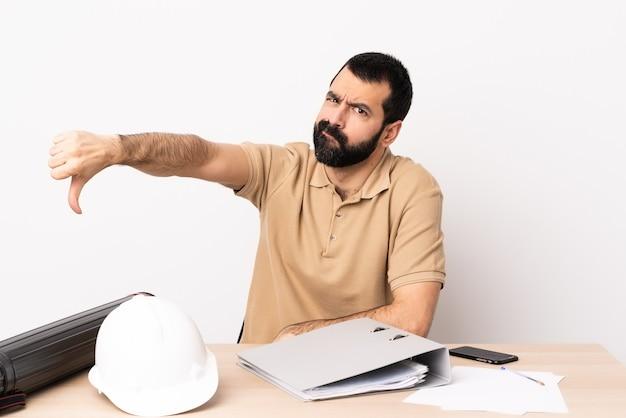 否定的な表現で親指を下に示すテーブルでひげを持つ白人建築家男。