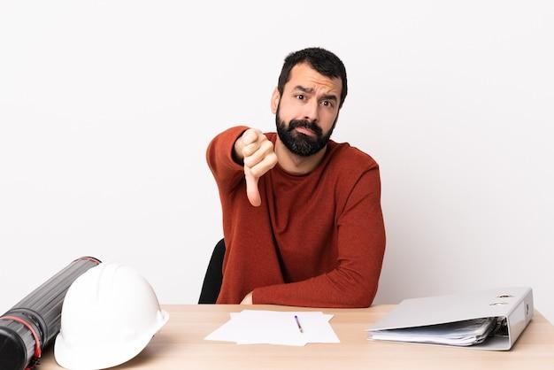 부정적인 식으로 아래로 엄지 손가락을 보여주는 테이블에 수염을 가진 백인 건축가 남자.