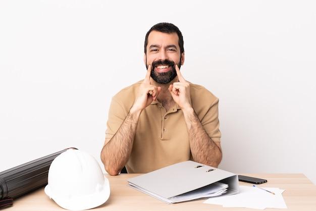 웃 고있는 테이블에 수염을 가진 백인 건축가 남자