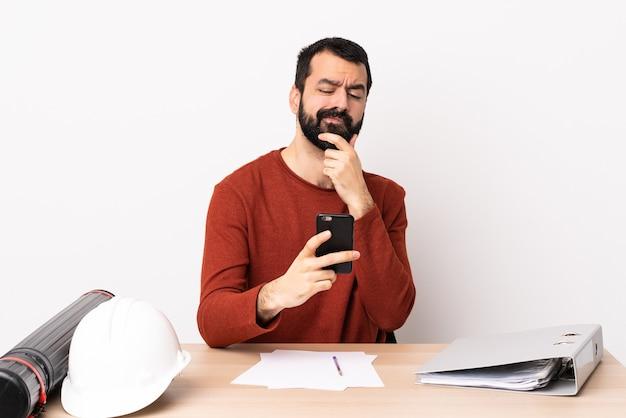 思考とメッセージを送信するテーブルのひげを持つ白人建築家男。