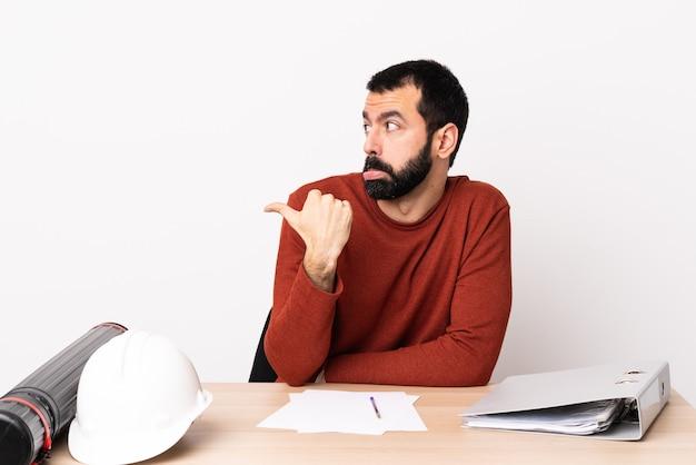 불행 하 고 측면을 가리키는 테이블에 수염을 가진 백인 건축가 남자.