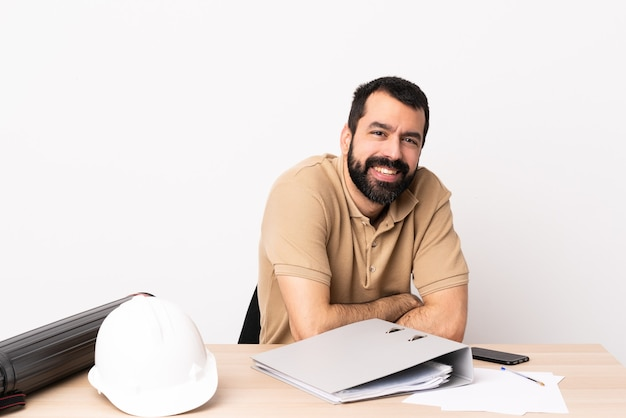腕を組んで、楽しみにしてテーブルにひげを生やした白人建築家の男。