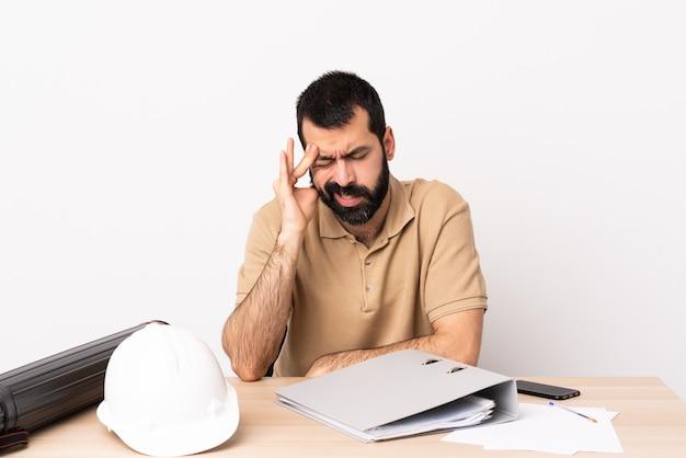 두통으로 테이블에 수염을 가진 백인 건축가 남자