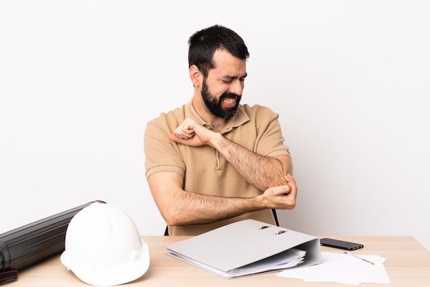 팔꿈치에 통증이 테이블에 수염을 가진 백인 건축가 남자.