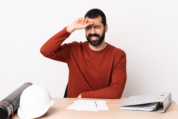 피곤하고 아픈 표정으로 테이블에 수염을 가진 백인 건축가 남자