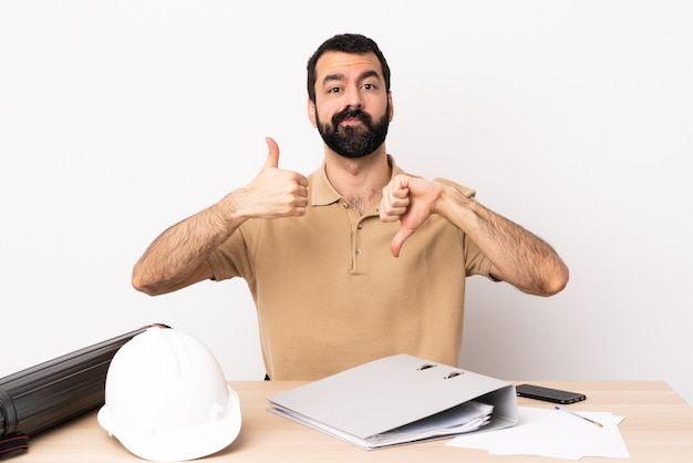 Caucasian architect man with beard in a table making good-bad sign. undecided between yes or not.