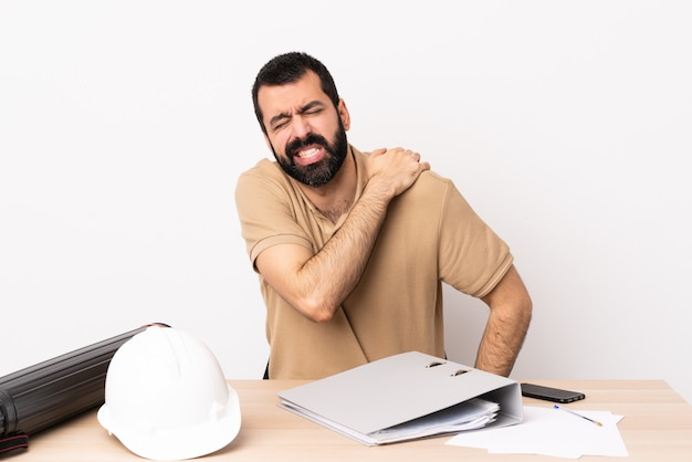 Caucasian architect man with beard in a table suffering from pain in shoulder for having made an effort