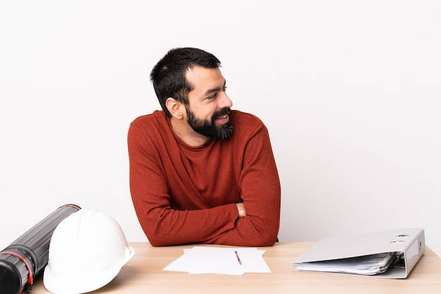 Caucasian architect man with beard in a table with arms crossed and happy.
