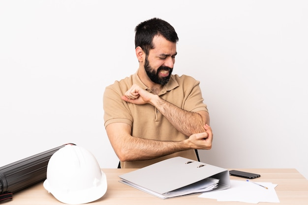 Caucasian architect man with beard in a table with pain in elbow.