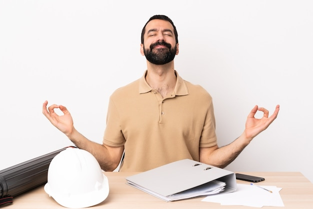 Caucasian architect man with beard in a table in zen pose.